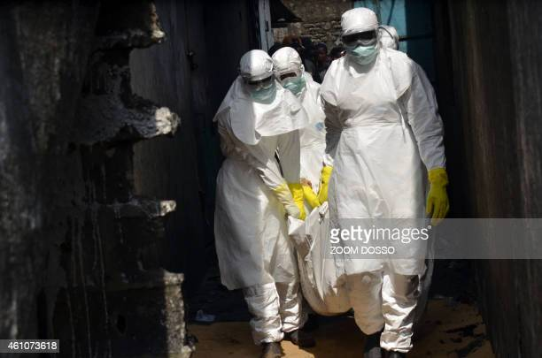 Red cross workers wearing protective suits carry the body of a person who died from Ebola during a burial with relatives of the victims of the virus...