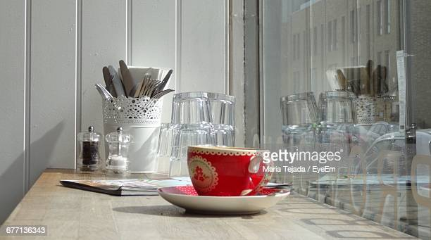 red cup and saucer on wooden table - maria tejada stock pictures, royalty-free photos & images