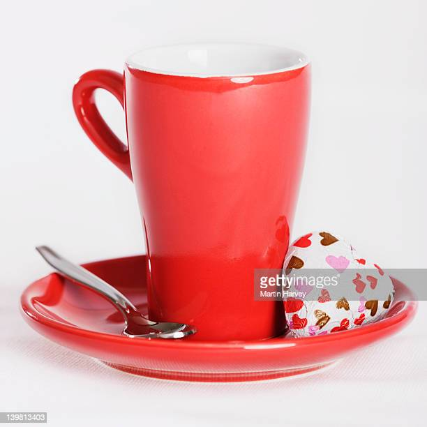 Red cup and saucer with love heart chocolate, against white background