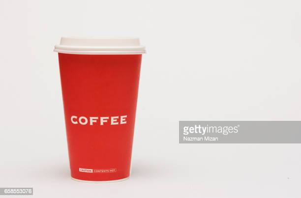 A red cup of coffee on white background.