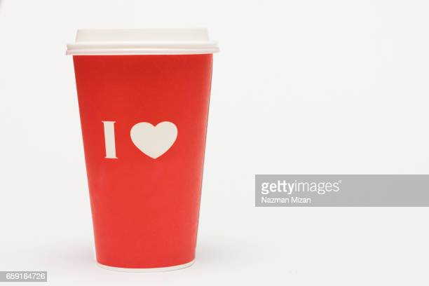 A red cup of coffee with love symbol on white background.