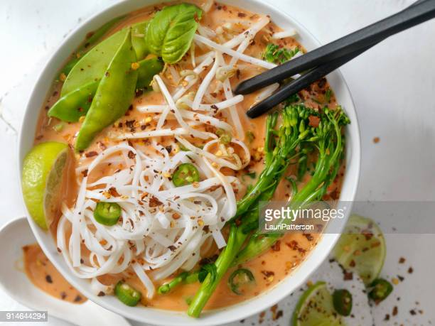 red curry noodle soup with broccolini, bean sprouts and fresh basil, - curry soup stock photos and pictures