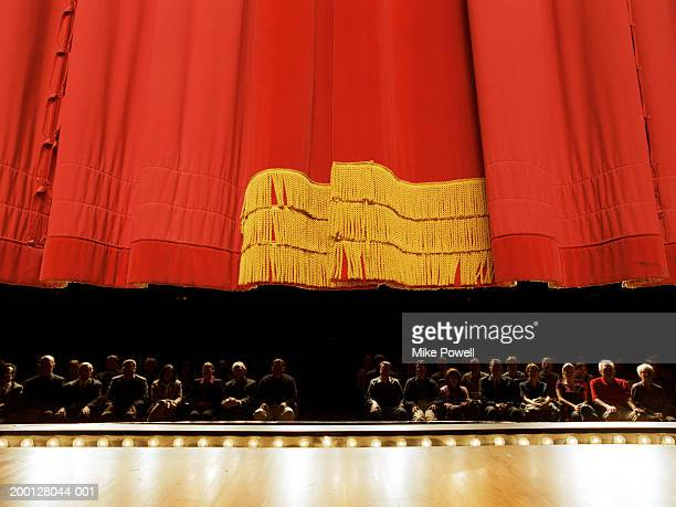 Red curtain descending on stage, audience in background