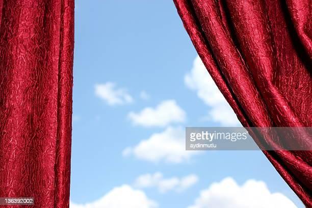 Des rideaux rouge et ciel nuageux