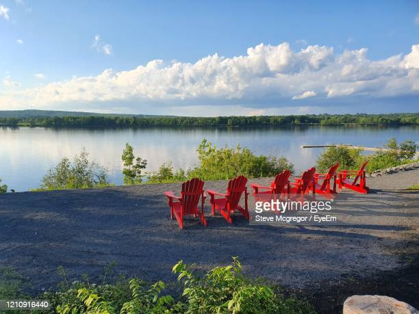 red deck chairs by the river. - mcgregor stock pictures, royalty-free photos & images