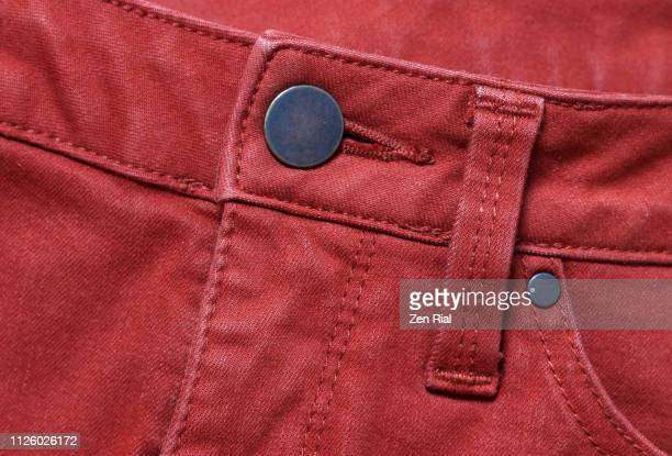 red denim jeans showing front metal button and belt loop and part of front pocket - red pants stock pictures, royalty-free photos & images