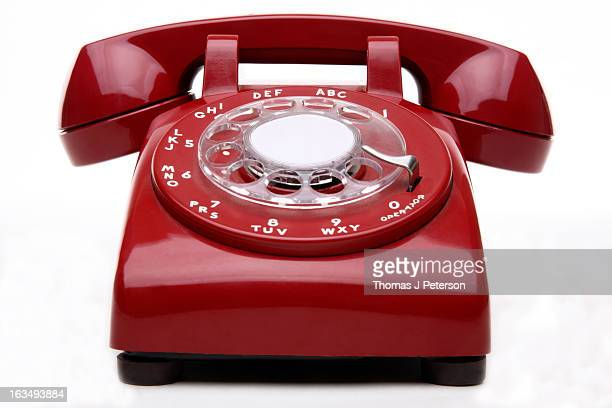 Red dial telephone on white background