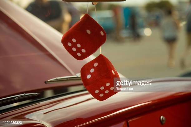 red dice hanging in a shiny red car - dice stock pictures, royalty-free photos & images