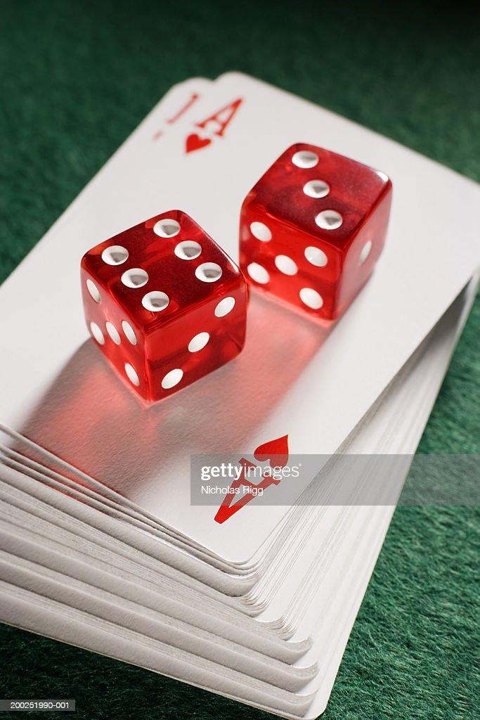 Red dice on pile of playing cards, close-up : Stock Photo