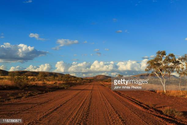 red dirt outback road near mount tom price. - remote location stock pictures, royalty-free photos & images