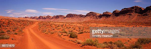 red dirt road beside comb ridge - timothy hearsum stock pictures, royalty-free photos & images