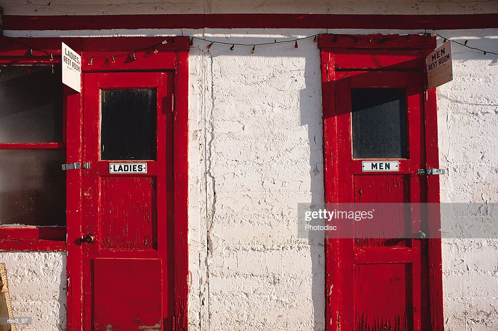 red doors and a window stand amidst white stucco walls : Photo
