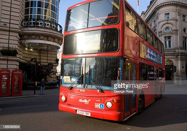 A red double deck bus rounds a corner in Piccadilly Square on November 19 2011 in London England An unusually warm day in Central London greeted...