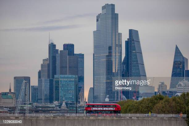 Red double-decker bus travels across the River Thames in front of skyscrapers in the City of London, U.K., on Monday, Oct. 12, 2020. The approach of...
