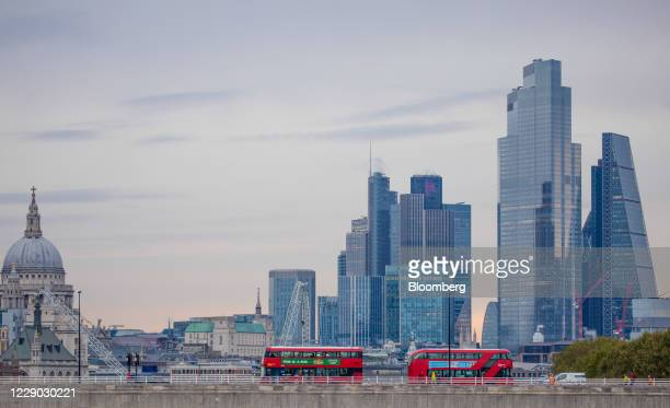 Red double-decker buses travel across the River Thames in front of skyscrapers and St. Paul's Cathedral in the City of London, U.K., on Monday, Oct....
