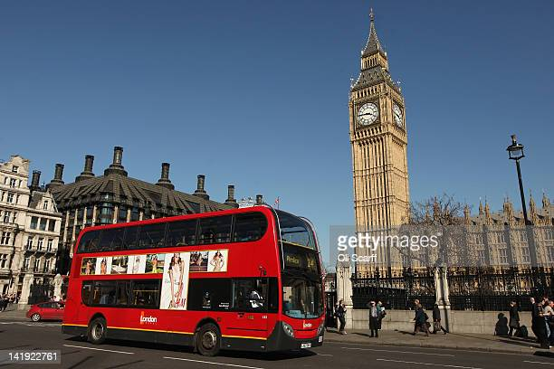 A red doubledecker London bus drives through Parliament Square on March 26 2012 in London England