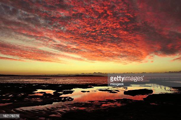 Red dramatic clouds at sunrise over Cronulla Beach