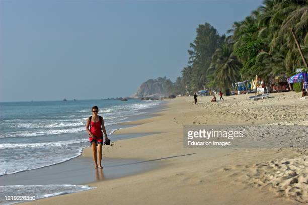 Red dress woman walks barefoot in waves early morning Lamai Beach Ko Samui island Thailand.