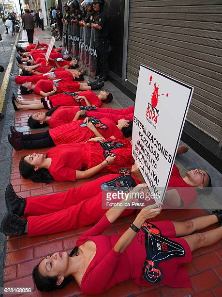 Red dressed activists women lying on the sidewalk from 'We are 2074 and many more' movement made a demonstration in front of the office of the...