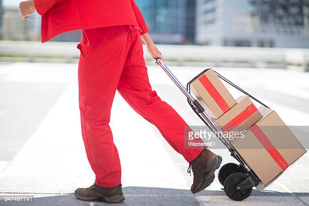 red dressed parcel deliveryman with parcels - red pants stock photos and pictures