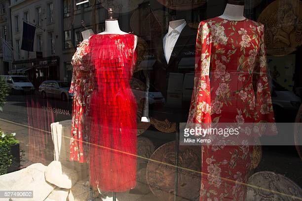 Red dresses for sale in the Dolce and Gabbana shop on Bond Street, London, UK. Dolce & Gabbana is an Italian luxury industry fashion house. The...