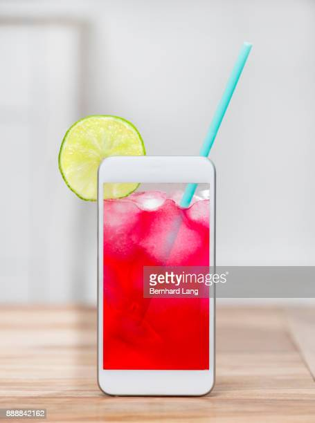 Red Drink on phone screen standing on table