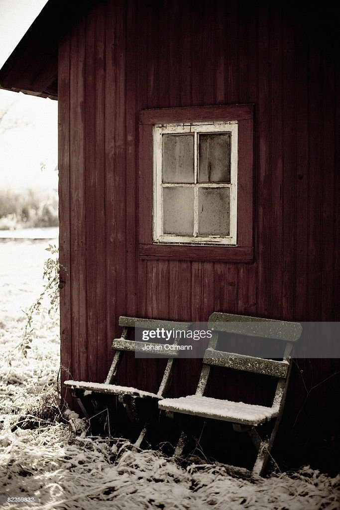 A red dry privy and two snowy chairs Gotland Sweden. : Stock Photo