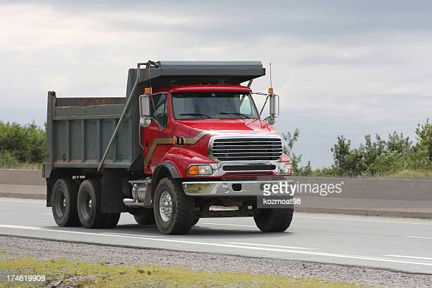 Red Dump Truck Travelling On Highway To A Construction Site