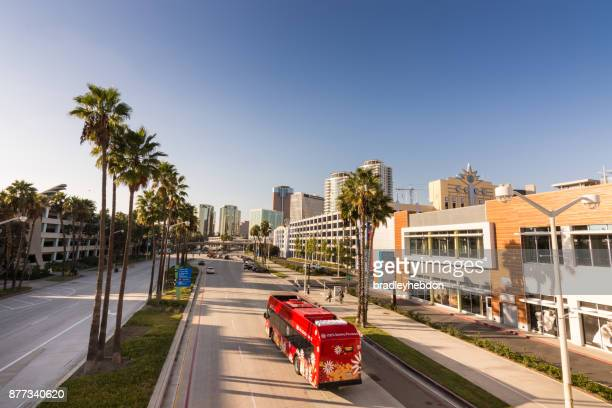 red electric bus driving in downtown long beach, ca - long beach california stock photos and pictures