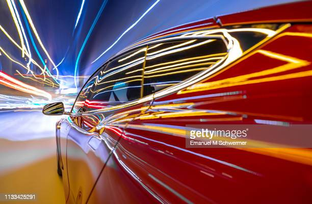 red electric powered car drives on city highway while night - streaking street lights. - elektroauto stock-fotos und bilder