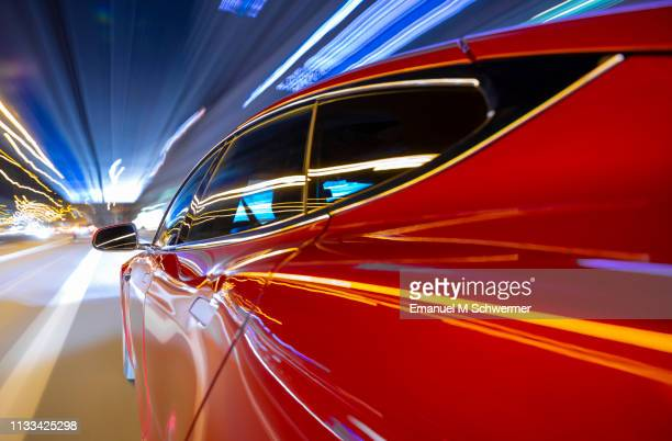 red electric powered car drives on city highway while night - streaking street lights and signs. - prestige car stock pictures, royalty-free photos & images
