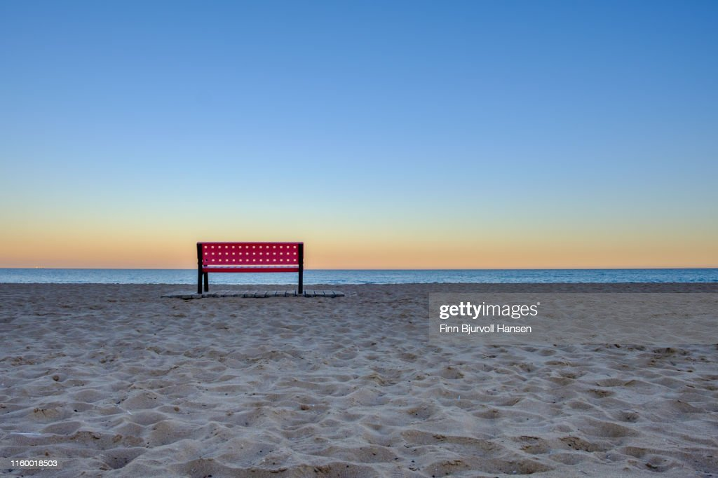 Red empty bench at the beach at sunset, sand in foreground and ocean in backround : Stock Photo