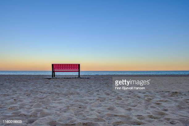 red empty bench at the beach at sunset, sand in foreground and ocean in backround - finn bjurvoll stockfoto's en -beelden