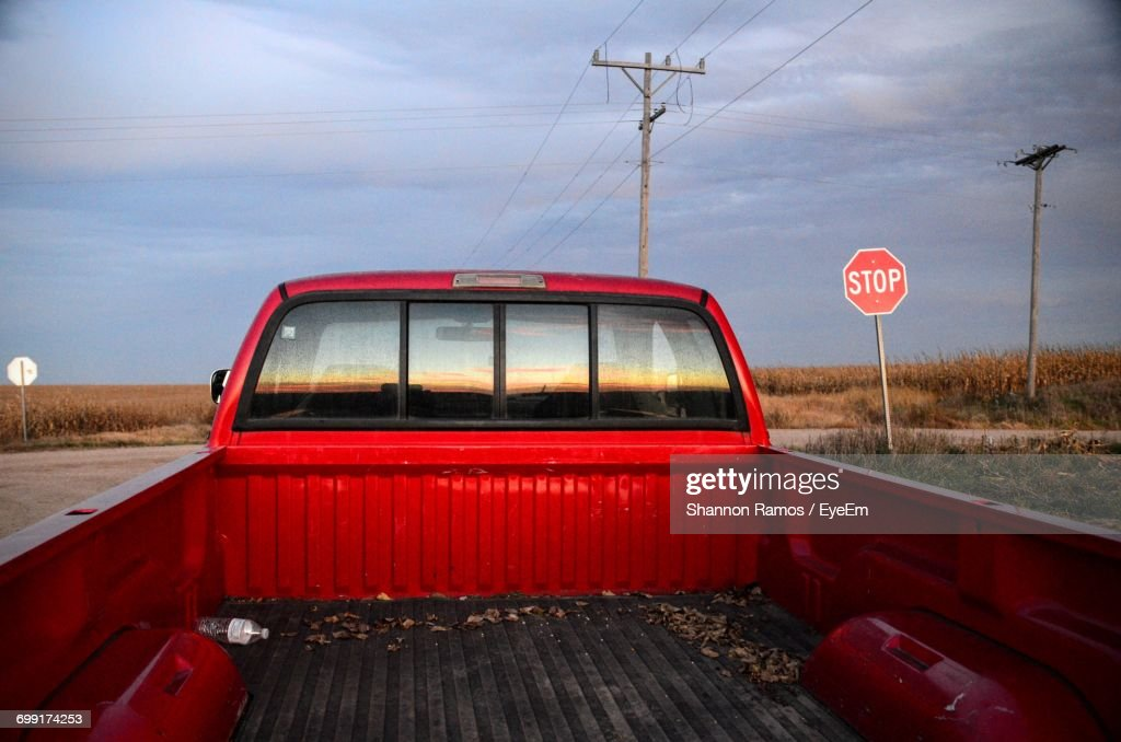 Red Empty Pick-Up Truck On Road Against Sky : Stock Photo