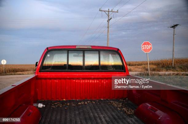 Red Empty Pick-Up Truck On Road Against Sky