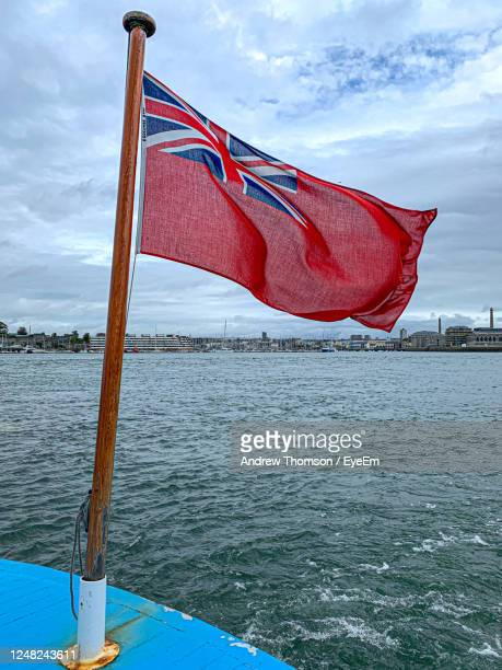 red ensign flag on flagpole on boat sailing in sea against blue sky background - insignia stock pictures, royalty-free photos & images
