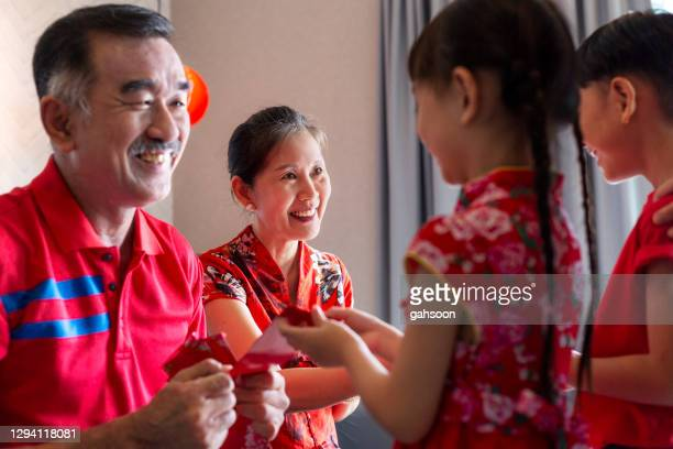 red envelope giving for chinese new years. grand parents and grandchildren bonding. - traditional clothing stock pictures, royalty-free photos & images