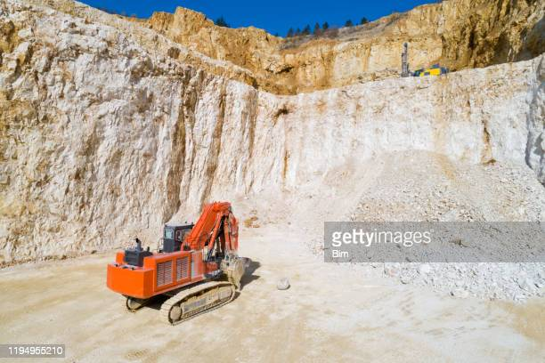 red excavator in a quarry, aerial low altitude view - construction material stock pictures, royalty-free photos & images