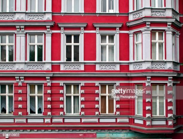 red facade of residential building in the district of kreuzberg in berlin, germany - altbau fassade stock-fotos und bilder