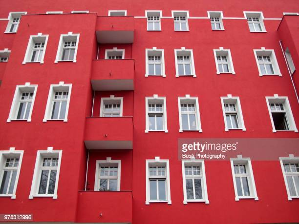 red facade of residential building in the district of neukoelln in berlin, germany - ベルリン ミッテ区 ストックフォトと画像