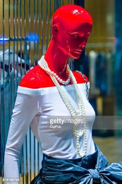 Red female like mannequin in white bare shoulder blouse and wearing long pearl necklace