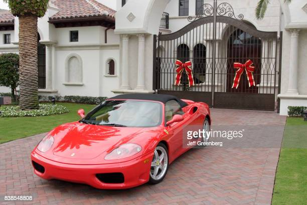 A red Ferrari on the driveway of an McMansion