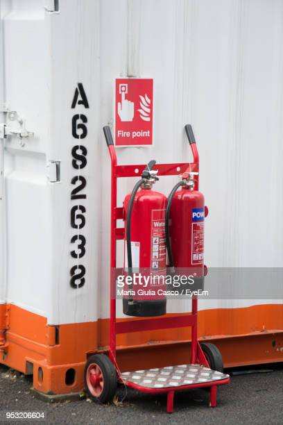 red fire extinguishers against text on cargo container - 消火器 ストックフォトと画像