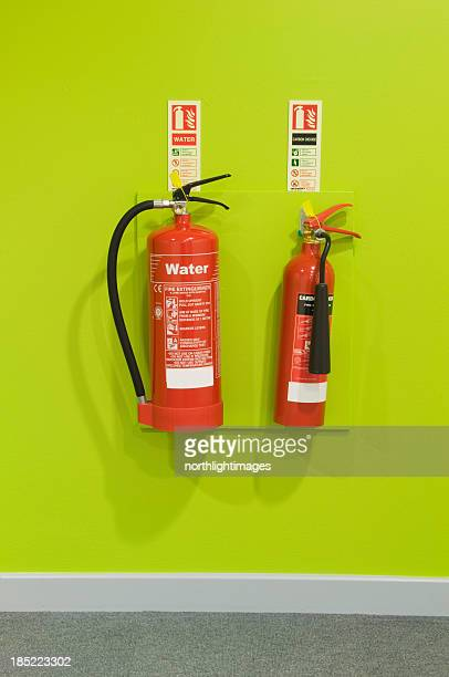 Red fire extinguishers on a green wall