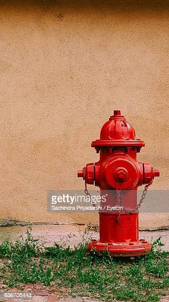 red fire hydrant against wall - fire hydrant stock pictures, royalty-free photos & images