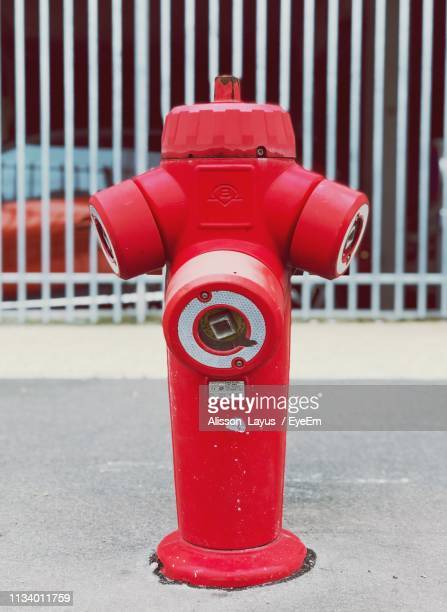 red fire hydrant on footpath against building - alisson stock pictures, royalty-free photos & images