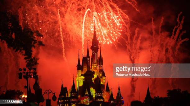 Red fireworks and yellow strobe lights illuminating the Cinderella Castle in the Walt Disney's Magic Kingdom themed park. The famous place is one of...
