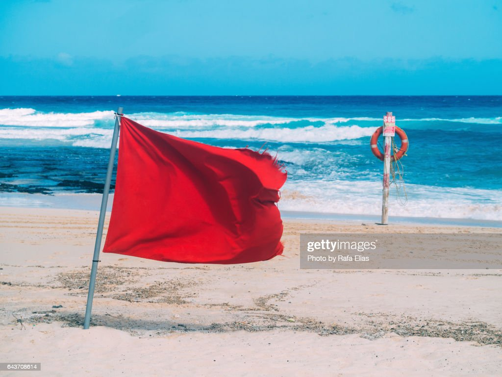 Red flag and lifebelt attached to post on the beach : Stock Photo