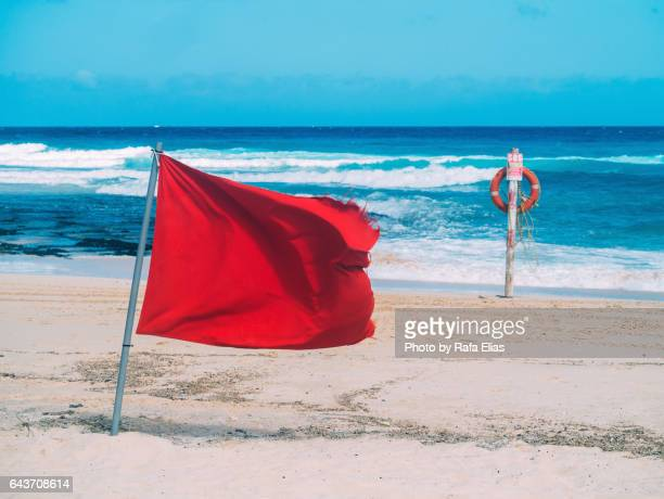 Red flag and lifebelt attached to post on the beach