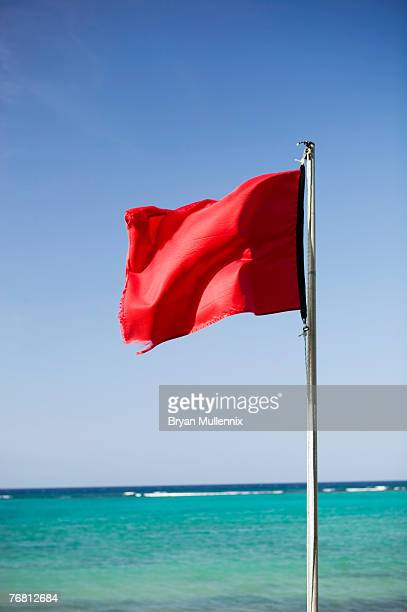 red flag and ocean, jamaica - flagpole stock pictures, royalty-free photos & images